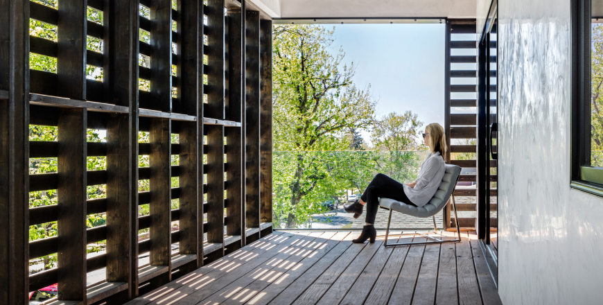 A lady sitting inside a room that has been designed by architects using pallets.